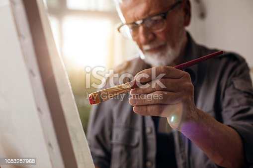 Close up shot of an older man painting on canvas