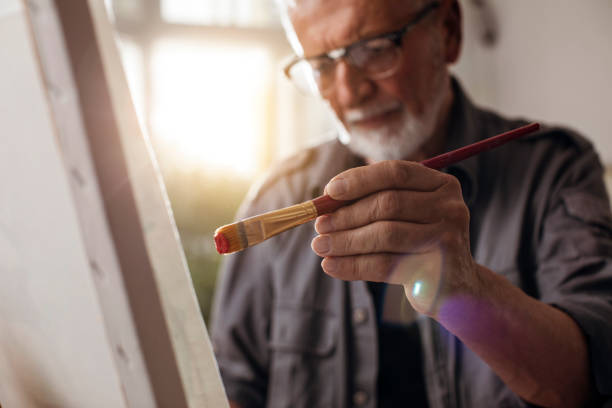 Portrait of a man painting Close up shot of an older man painting on canvas hobbies stock pictures, royalty-free photos & images