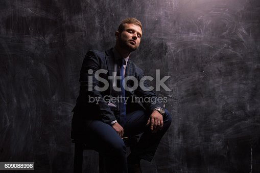 471947536 istock photo Portrait of a man sitting on a chair 609088996