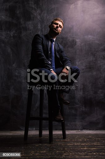 471947536 istock photo Portrait of a man sitting on a chair 609089066