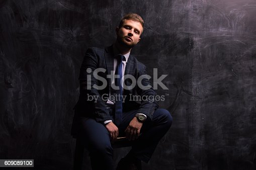 471947536 istock photo Portrait of a man sitting on a chair 609089100