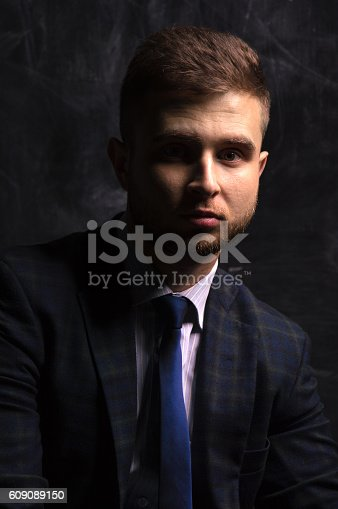471947536 istock photo Portrait of a man sitting on a chair 609089150
