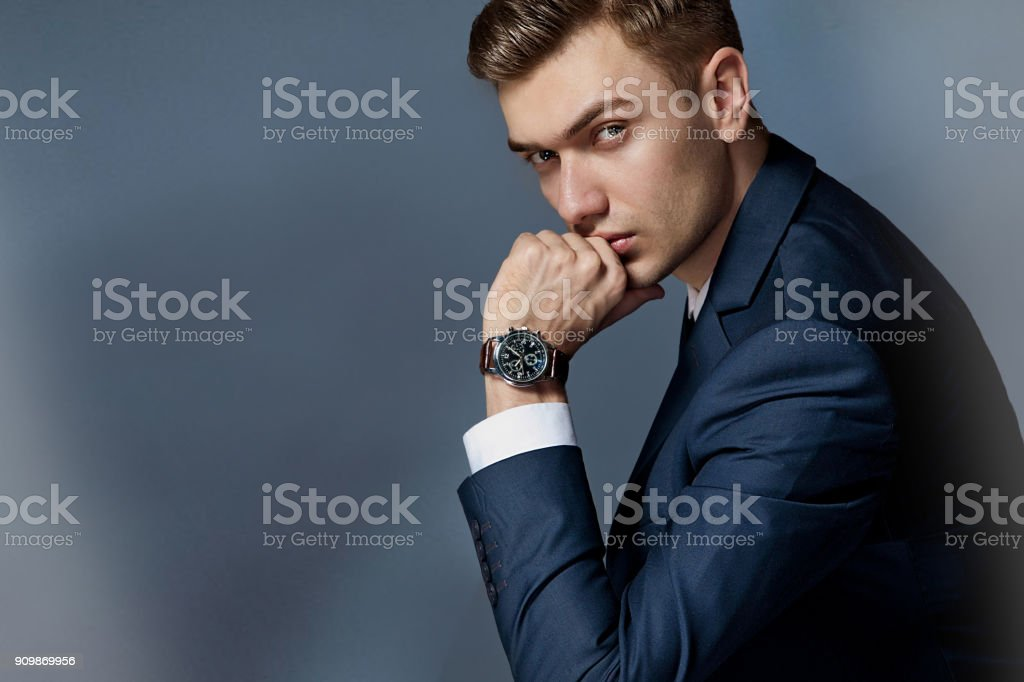 portrait of a man sitting with a suit with a watch, studio stock photo