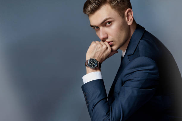 portrait of a man sitting with a suit with a watch, studio - handsome people stock photos and pictures