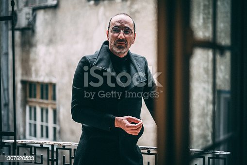 Close up of a handsome mature man with eyeglasses on the balcony smoking a cigarette