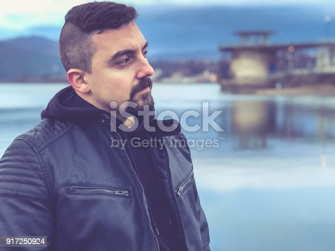 istock Portrait of a man standing on a lake's beach and contemplating 917250924
