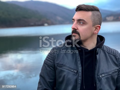 istock Portrait of a man standing on a lake's beach and looking away 917250954
