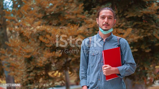 Portrait of a man wearing a medical mask on a student campus. Coronavirus outbreak, Getting ready for class.
