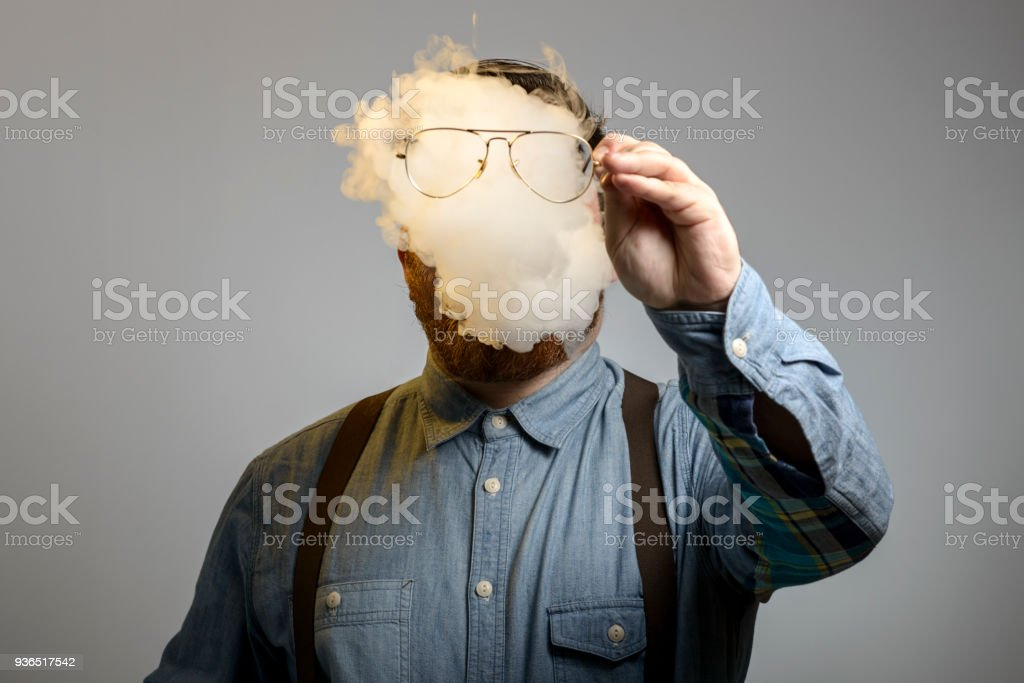 portrait of a man who is smoking an e-cigarrette stock photo