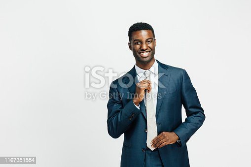 973213156istockphoto Portrait of a man with a big smile and hands on tie 1167351554