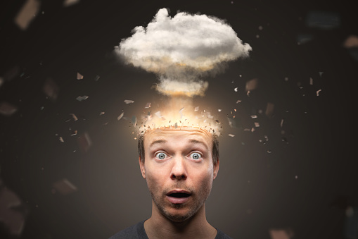 A man looking into the camera with a shocked expression. The top of his head is exploding in a non cruel way. A mushroom cloud is rising above the head.