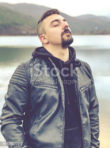 istock Portrait of a man with closed eyes standing on a lake's beach 917250772