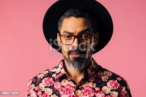 Portrait of a man with beard, hat  and glasses, isolated in a studio background