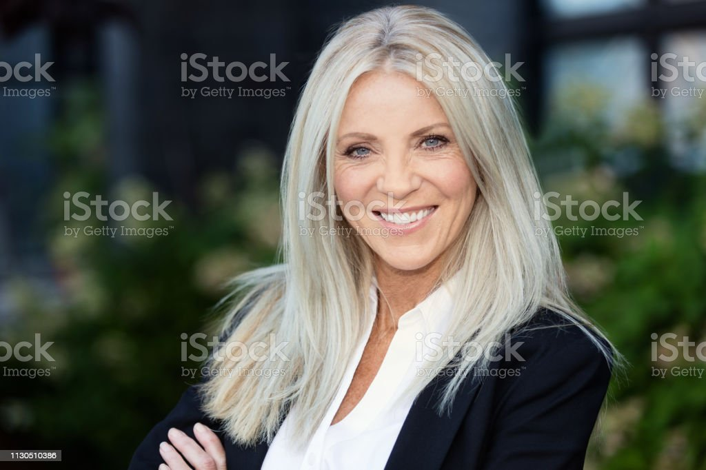 Portrait Of A Mature Blonde Businesswoman Smiling. Outside the office Portrait Of A Mature Blonde Businesswoman Smiling. Outside the office. She is happy, arms crossed 40-49 Years Stock Photo