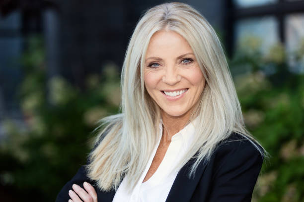 Portrait Of A Mature Blonde Businesswoman Smiling. Outside the office stock photo
