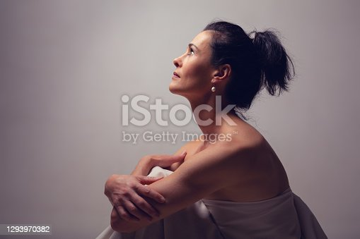 istock Portrait of a mature brunette woman sitting and contemplates the realities of life 1293970382