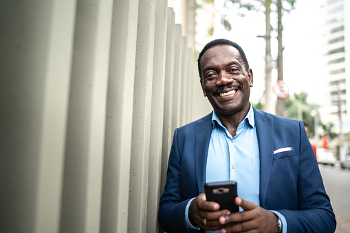 Portrait of a mature businessman using mobile phone at city