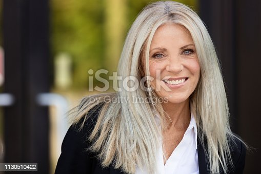 Portrait Of A Mature Businesswoman Smiling. She is stylish and happy