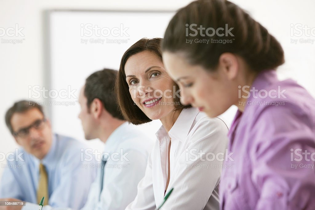 Portrait of a mature businesswoman with colleagues in meeting royalty-free stock photo