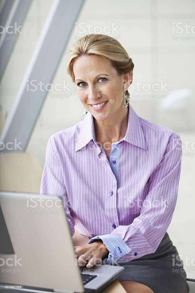 Portrait of a mature businesswoman working on laptop at office royalty-free stock photo