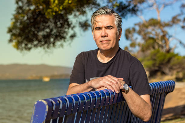 Portrait of a mature man 57 years with gray hair looking camera sitting on a bench at a beach outdoors, confident, relaxed stock photo