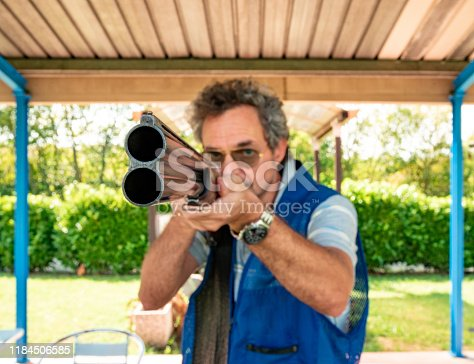 Portrait of a Mature Man Aiming With Double Barrel Shotgun on Shooting Range Outdoors.