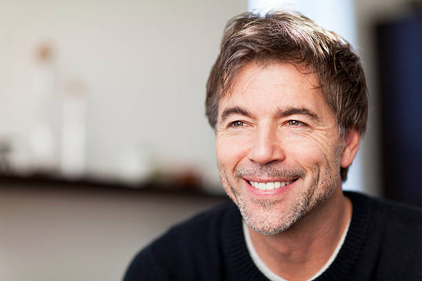 Portrait Of A Mature Man Smiling And Looking Away. Home. stock photo
