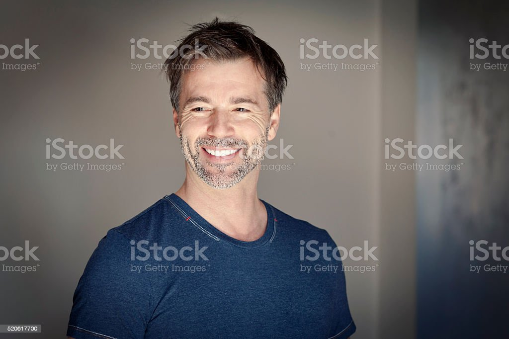 Portrait of a mature man smiling and looking away stock photo
