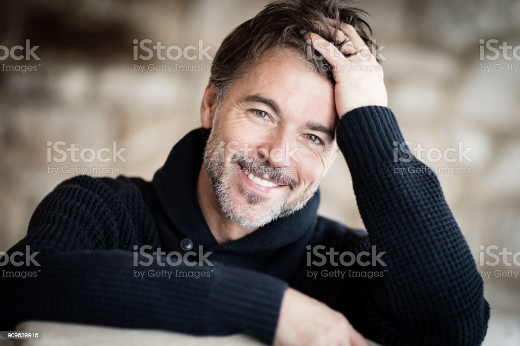 Portrait Of A Mature Man Smiling At The Camera. Home stock photo