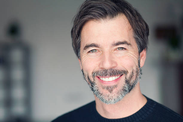 portrait of a mature man smiling at the camera - teeth stock photos and pictures