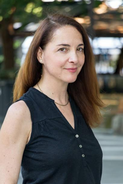 porträtt av en mogen kvinna, 40s, ser kamera med mjukt leende, utomhus i en stad. - profile photo bildbanksfoton och bilder