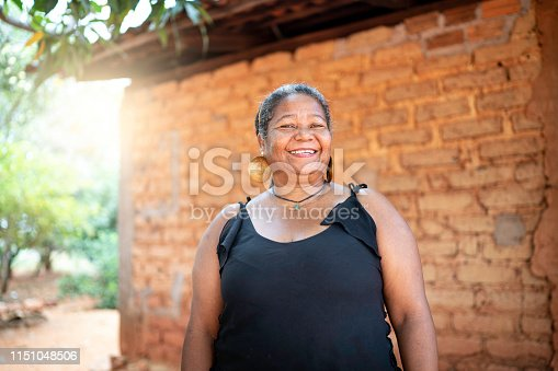 Portrait of a mature woman in front of a wattle and daub house