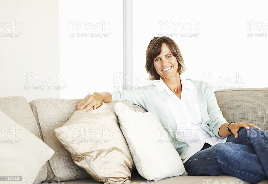 Portrait of a mature woman sitting on couch royalty-free stock photo