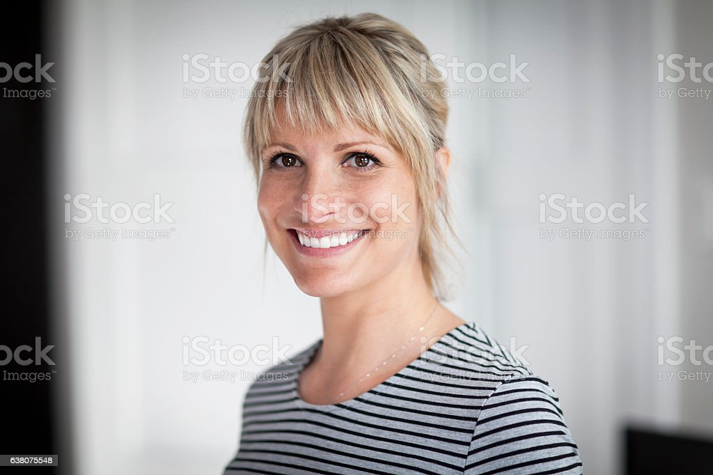 Portrait Of A Mature Woman Smiling At The Camera At Home stock photo