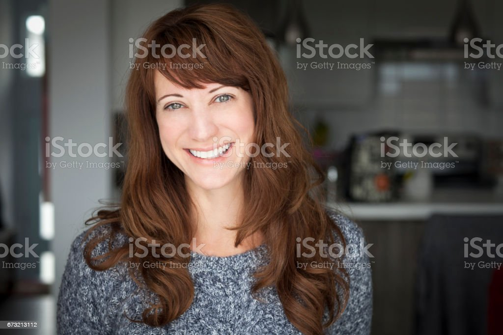 Portrait Of A Mature woman smiling At The Camera. In the kitchen. stock photo