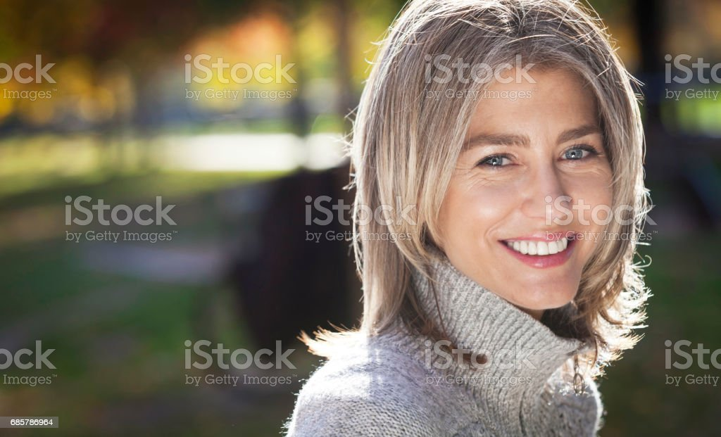 Portrait Of A Mature Woman Smiling At The Camera. Outside. Gray hairs. stock photo