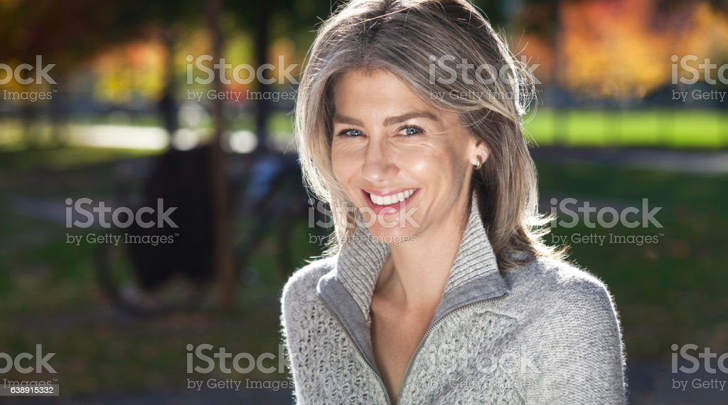 Portrait Of A Mature Woman Smiling At The Camera. Outside. stock photo