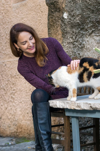 Portrait of a mature woman wearing high knee black boots and a purple dress, caressing a cat. stock photo