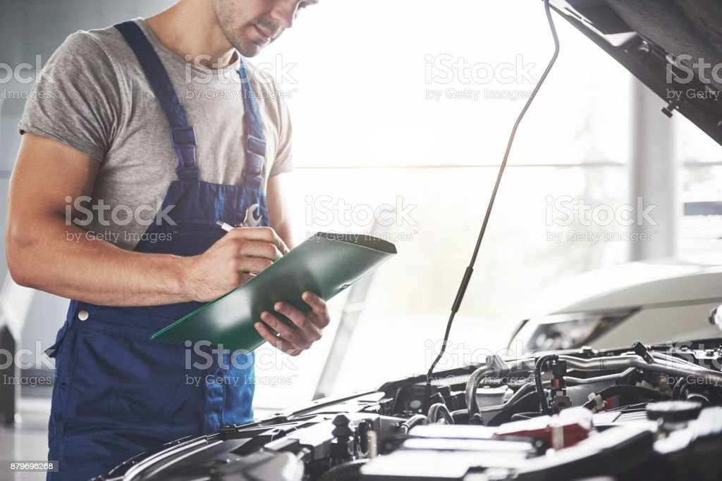 Portrait of a mechanic at work in his garage - car service, repair, maintenance and people concept - foto stock