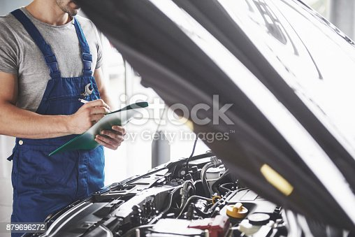 962888586 istock photo Portrait of a mechanic at work in his garage - car service, repair, maintenance and people concept 879696272