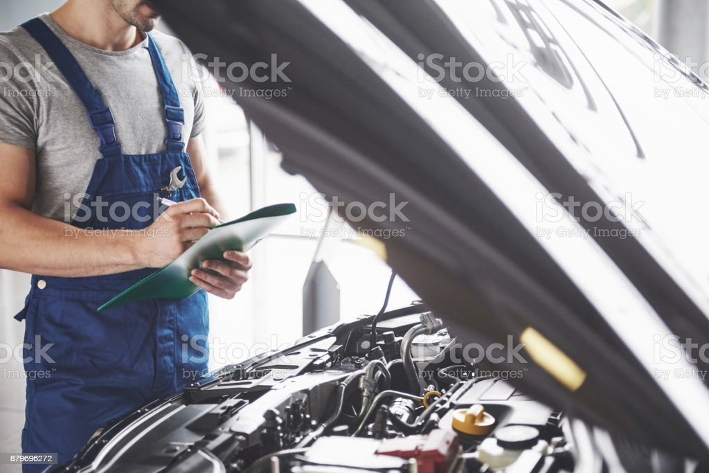 Portrait of a mechanic at work in his garage - car service, repair, maintenance and people concept stock photo
