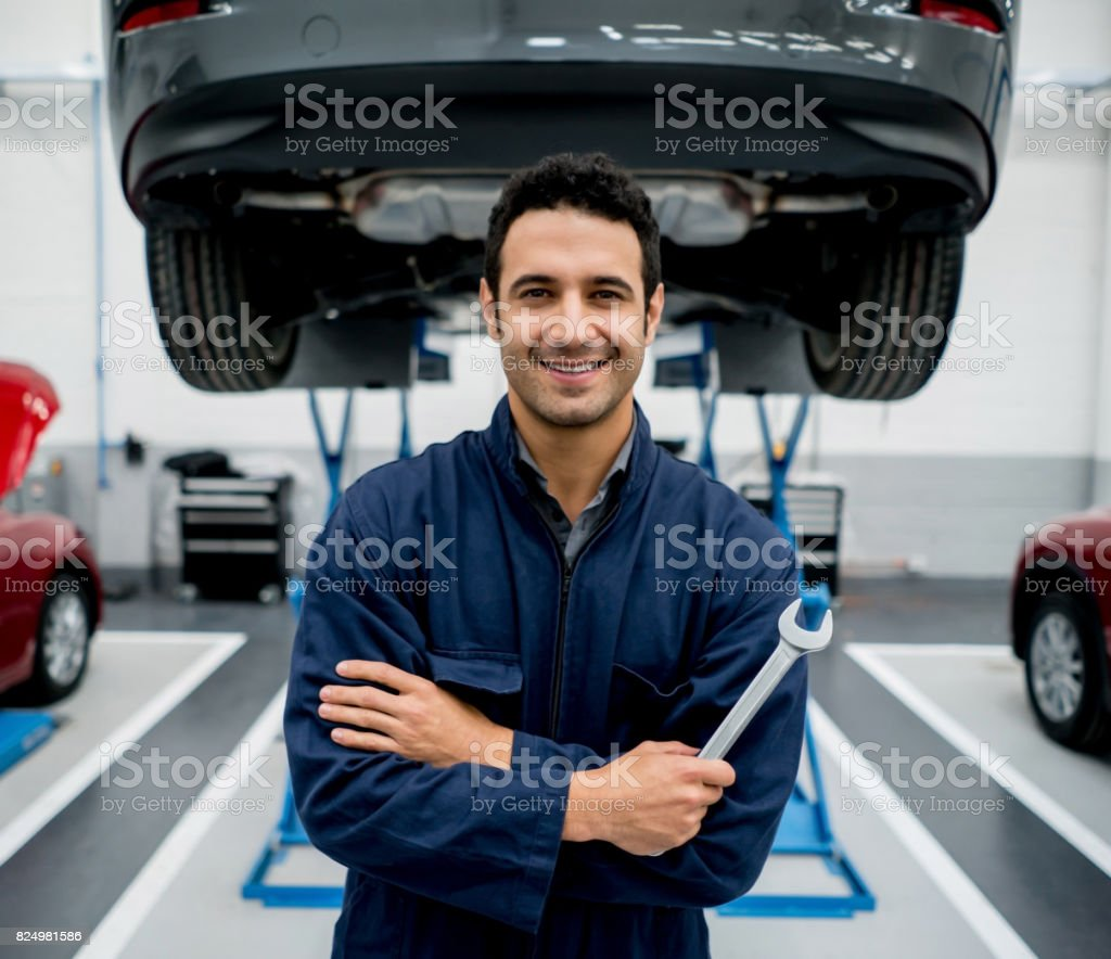 Portrait of a mechanic fixing cars at an auto repair shop stock photo