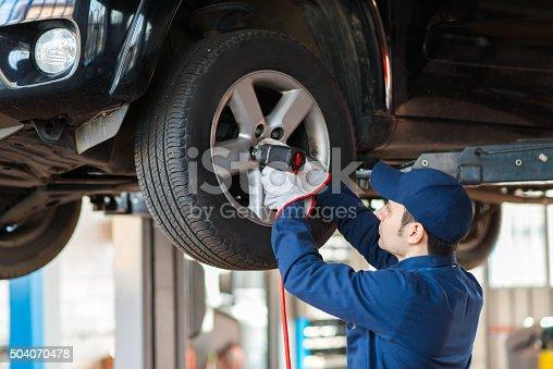 istock Portrait of a mechanic replacing wheel 504070478