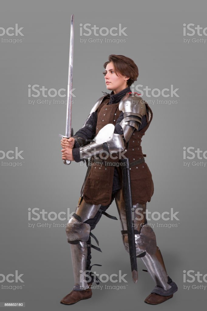 portrait of a medieval female knight in armour over grey background stock photo