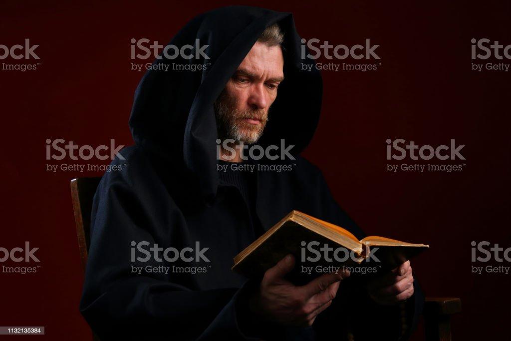 Retrato de uma monge medieval com um livro em um fundo de Borgonha - foto de acervo