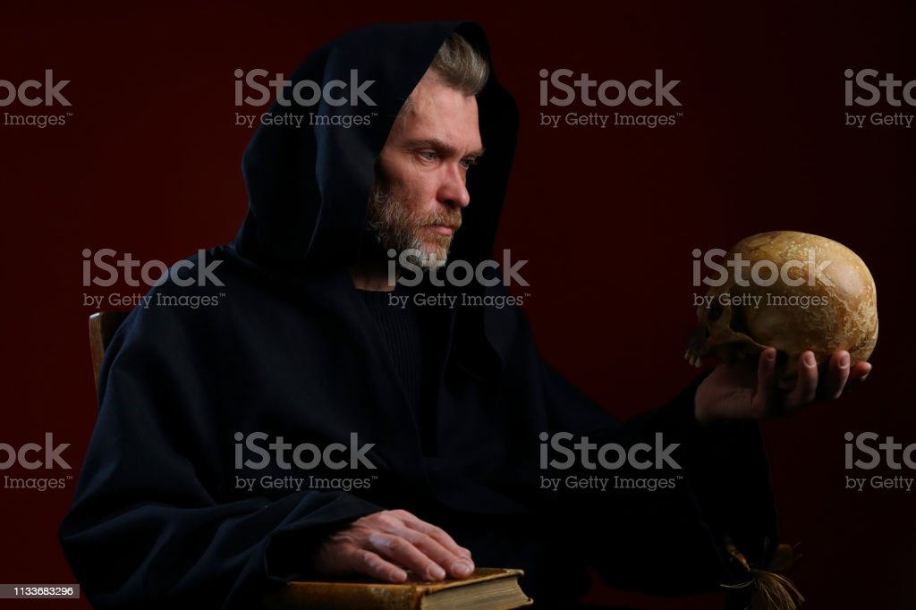 Retrato de uma monge medieval com um crânio em suas mãos - foto de acervo