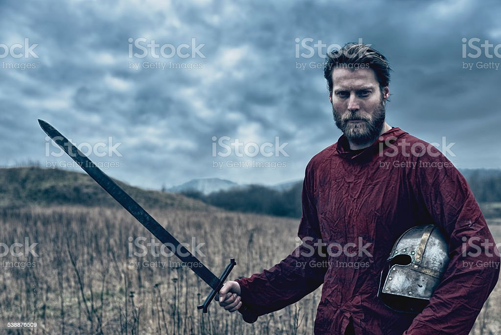 Portrait of a medieval warrior with sword and helmet stock photo