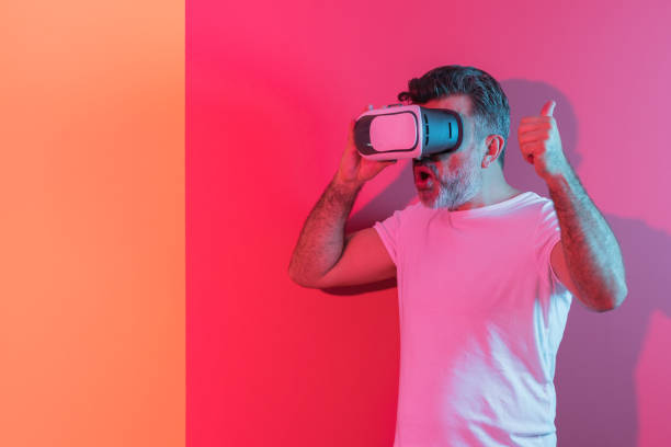 portrait of a mid adult man with vr headset experience - vr red background imagens e fotografias de stock