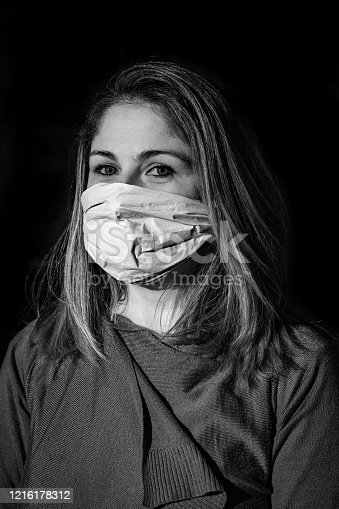 Black and white portrait of a woman wearing a surgical mask on a total black background.