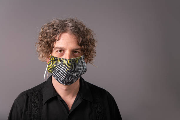 Portrait of a middle aged man wearing a homemade cloth mask. He looks at the camera. stock photo